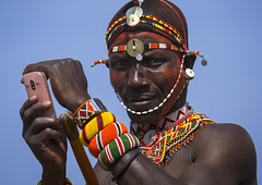 Rendille Tribesman Taking Picture With His Mobile Phone, Turkana Lake, Loiyangalani, Kenya (Eric Lafforgue) Tags: africa shirtless portrait people beauty horizontal closeup outdoors person photography necklace day adult kenya african candid earring pride tribal headshot jewellery communication smartphone human mobilephone warrior wirelesstechnology ornate tribe moran hairstyle samburu cultures beautifulpeople adultsonly oneperson headdress headwear kenyan eastafrica rift traditionalclothing realpeople turkana colorimage lookingatcamera onlymen onemanonly waistup colourimage 1people indigenousculture rendille loiyangalani ethny rendile turkanalake colourpicture usingphone portableinformationdevice kenya201400552