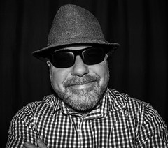 Portrait of a checked shirt man. (CWhatPhotos) Tags: photographs man male portrait self selfie me mine smile checked shirt checky hat tweed trilby wool fisheye view prime night time have it photograph pics pictures pic picture image images foto fotos photography artistic that which contain digital dark cwhatphotos 9mm bodycap body cap 9 mm lens olympus e5 mk2 omd shades sunglasses sun glassses specs