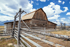 fenced & falling (almostsummersky) Tags: log grovont johnmoultonbarn mormon homestead summer johnmoultonhomestead mormonrowhistoricdistrict grandtetons mountainrange weathered jacksonhole farm valley wood building wooden nationalpark mountains grandtetonnationalpark clouds barn abandoned gambrelbarn fence gate settlement mormonrow afternoon grosventre antelopeflats plain tetonrange sky wyoming moose unitedstates us