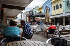 Enjoying Afternoon Tea (Jocey K) Tags: newzealand christchurch buildings city signs architecture people street newregentst cafes chairs tables clouds shops mural sky