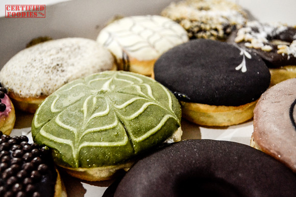 J.CO Donuts Green Tease surrounded by chocolate flavors