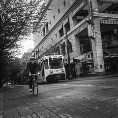 Home To The Finish Line (TMimages PDX) Tags: iphoneography photography image photo photograph streetscene fineartphotography geotagged people urban city street streetphotography portland pacificnorthwest sidewalk pedestrians buildings avenue road blackandwhite monochrome vignette bicycle biking train transportation