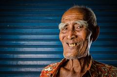 Mr. Wayan Tengkong (eggysayoga) Tags: old portrait bali man smile face closeup indonesia nikon funny unique teeth rage meme portraiture eyebrow troll kit softbox eyebrows batik denpasar wayan trollface strobist 18105mm yongnuo d7000 9gag qianite tengkong