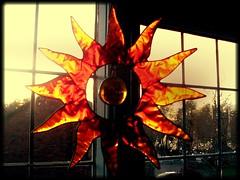 the inner sun (wikkanman) Tags: red orange sun window yellow reflecting solar ornament shining