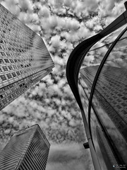 Canary Wharf Reflections (david.kittos) Tags: blackandwhite bw reflection building london architecture clouds plane reflections canarywharf zd 1260mm olympusmagazine