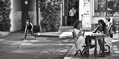 Zwei Frauen sitzen in einem Berliner Hinterhof in einem Café und unterhalten sich. Hinter ihnen, auf der anderen Seite des Bildes, springt eine Frau eine Boule Kugel hinterher. (kohlmann.sascha) Tags: street people woman house plant building nature shop bar landscape toy restaurant store cafe backyard natur pflanze streetphotography haus menschen laden frau landschaft caf spielzeug kneipe brasserie urbanlandscape gasthaus hinterhof mensch rasthaus gastwirtschaft stadtlandschaft streetfotografie gebude geschft speiselokal speisehaus stra§enfotografie speisewirtschaft berlinerstra§enszene