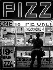 NYC Bargain - Pizza (Bob Jagendorf) Tags: newyorkcity blackandwhite bw food woman man sign night store pizza eat vision:text=074