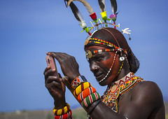 Rendille Tribesman Taking Picture With His Mobile Phone, Turkana Lake, Loiyangalani, Kenya (Eric Lafforgue) Tags: africa shirtless portrait people flower beauty horizontal closeup outdoors person photography necklace day adult kenya african candid feather earring pride tribal headshot jewellery communication smartphone human mobilephone warrior wirelesstechnology ornate tribe moran hairstyle samburu cultures beautifulpeople adultsonly oneperson headdress decorated headwear kenyan eastafrica rift traditionalclothing realpeople turkana colorimage onlymen onemanonly colourimage 1people indigenousculture rendille loiyangalani ethny rendile turkanalake colourpicture usingphone portableinformationdevice kenya201400562