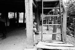 Hiding (pacco_racco) Tags: boy hidding house middlemekong northernlaos leicam6 leicasummicron35mmf20asph kodaktrix400