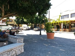 (Psinthos.Net) Tags:  psinthos village square psinthossquare psinthosvillage    villagecenter      stonewall   cars day sunnyday light sunlight     shadow pot  treetrunk   trees  treebranches  road greenery   umbrellas noon    autumn october