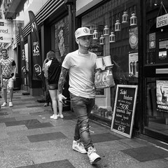 Cap and Tattoos (Howie Mudge LRPS) Tags: man tattoos sleeve cap hat walk walking serious casual candid portrait street streetphotography streetlife blackandwhite blackwhite mono monochrome monochromatic shops signs people men woman pavement windows doors cardiff caerdydd city center capital wales cymru uk travel travelling traveller sonydscrx100m4 pointandshootcamera compactcamera sonyrx100iv