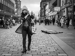 Call Of The Wild (Leanne Boulton) Tags: monochrome outdoor urban street candid portrait streetphotography candidstreetphotography candidportrait eyecontact candideyecontact streetlife woman female face facial expression look emotion feeling walking boots eyes hat mobile phone tone texture detail depth natural light shade shadow city scene human life living humanity people society culture canon 7d wideangle black white blackwhite bw mono blackandwhite glasgow scotland uk