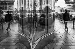 Just another day in the multiverse (R A Pyke (SweRon)) Tags: street woman walking window reflection drottninggatan rebro orebro sweden 201209201469 sweron blackandwhite bw pentax k5 samyang14mmf28