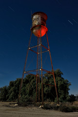 water tower. calipatria, ca. 2016. (eyetwist) Tags: eyetwistkevinballuff eyetwist watertower water abandoned farm agriculture calipatria saltonsea night desert dark nikon nikond7000 d7000 nikkor capturenx2 1024mmf3545g 1024mm fullmoon photography gel tripod npy nocturne longexposure derelict lightpainting red flashlight ruin decay california imperial sonorandesert salton sea startrails american west ca111 imperialvalley niland farming alfalfa tank tower old girder hardware truss steel landscape