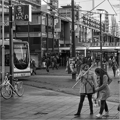 Wrapping to do (John Riper) Tags: johnriper street photography straatfotografie square vierkant bw black white zwartwit mono monochrome netherlands candid john riper xt1 fuji 18135 tram carnisselanden van oldenbarneveltstraat oldenbarneveltplaats lijnbaan women wrapping paper ladies people l kfc perry wok to go coolcat bicycles ret binnenwegplein