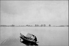 The Boat Man & Cloudless Skies (*iris-hues*) Tags: woman white black canon landscape grey photographer image indian horizon stock traveller process woodenboat paddling seller boatman shikara faraway emptysky lakenagin eos7d skeletalmess traditionalboatsofkashmir glasslighthues gettyimagesindiaq4 glhartdecor glhad