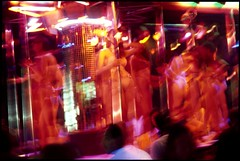 Prostitutes dance for prospective clients in a bar in the red-light district, Pat Pong, Bangkok, Thailand. (axlright) Tags: show travel tourism club thailand asia pat prostitution backpacking strip experience thai pong prostitutes strippers travelogue