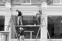 New Shop, New Sign (Cris Ward) Tags: uk blackandwhite bw london monochrome sign shop contrast digital work painting 50mm prime store britain furniture sony working monotone decorating signage desaturated ladder renovation alpha f18 dslr amateur beginner greyscale tradesmen a450 50mmdtsam