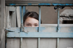 peeping (Amickman) Tags: portrait girl strange face look wall female asian outdoors hope freedom see interesting eyes break play action board watch grain stranger crack teen hide spy surprise mysterious getty opening curious scared breakthrough gazing peeking plank viewing obstacle gettyimages peeping detective gettyimage