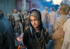 An iranian shiite muslim woman stands in front a bonfire after rubbing mud on her chador during the kharrah mali ritual to mark the ashura day, Lorestan province, Khorramabad, Iran (Eric Lafforgue) Tags: 9people adultsonly ashura celebration ceremony chador colorimage commemoration culture festival groupofpeople horizontal hussain imamhussein iran islam kharrahmali khorramabad lookingatcamera memorialevent men middleeast mourning mud mudrubbing muharram muslim outdoors people persia persian religion religious ritual shia shiism shiite tradition traditional veil veiled waistup woman lorestanprovince