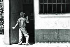 Alive in a world of rectangles (Pejasar) Tags: boy child blackandwhite bw rectangles framed messenger kid student school rural eltesoro guatemala jeans cap concreteblocks bars darkandlight