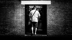 Going In (Sean Batten) Tags: london england unitedkingdom gb shoreditch bricklane blackandwhite bw nikon df 58mm person wall streetphotography street city urban