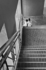 Bonding Time (FotoGrazio) Tags: friends people blackandwhite love stairs contrast couple friendship affection geometry fineart philippines touch streetphotography younglove streetscene stairwell together staircase manila filipino youngcouple bestfriends bonding socialdocumentary ruleofthirds leadinglines pacificislanders documentaryphotography shadesofgray sittingtogether touchingeachother fotograzio waynegrazio