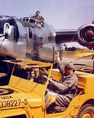 Control jeep occupants direct a Consolidated B-24 to the runway for take-off at a base in England.