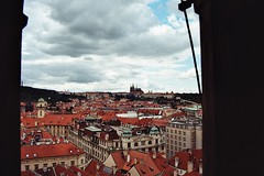 Rooftops in Prague (Notquiteahuman1) Tags: prague praha roofs rooftops townhall castle praguecastle prask hrad kodakgold200 nikonf501 sigma287013545af analog film kodak cathedral ancient history europe saintvituscathedral town city dramatic sky dramaticsky clouds coupolas blue white red bohemia roman czechoslovakia czechrepublic capital historic nikon flickr light overcast landscape urban prak streets houses old new framed window dcher tschechien himmel wolken telhados praga cenrio cu castelodepraga gold200