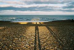 We Looked Like Giants (Kym Ellis) Tags: uk sea film beach analog seaside waves shadows friendship 28mm shingle pebbles eastbourne afga eos3000