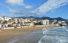 Sunny November (angelsgermain) Tags: morning november beach sun sea waves sand water houses promenade palmtrees church sky clouds hills platjadesantsebasti sitges catalonia catalunya