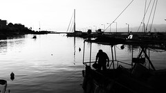 End of the day (jimiliop) Tags: fisherman boat calm sea water port job fishing working ripple town hometown cityscape bw sails kiato greece shadows contrast blackwhite man afternoon