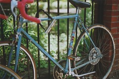 CCM (Ali Seglins) Tags: city pink blue summer toronto ontario canada green film bike bicycle analog 35mm fence cycling downtown lock bricks wheels sunny racing fujifilm kensingtonmarket canona1 handlebars ccm aliseglins targa5