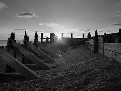 monochrome sunset (cngphotographic) Tags: ryeharbour nature reserve winchelsea eastsussex sunset sunshine shingle beach winter england britain outside outdoor monochrome linux opensource raw rawtherapee groynes shoreline timber seaside sea defences clouds blackandwhite shadows mono evening