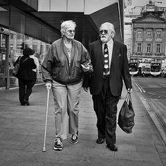 Walking Conversation (Peter.Bartlett) Tags: street city people urban blackandwhite woman man monochrome pen walking manchester mono blackwhite couple unitedkingdom candid streetphotography olympus walkingstick elderly nik olympuspen blackdiamond ep3 m43 blackwhitephotos streetphotographyurban fragmentsoftime niksilverefex microfourthirds peterbartlett olympuspenep3
