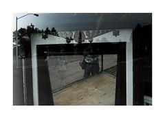 Shop window, Two Harbors, Minnesota (Richard C. Johnson: AKA fishwrapcomix) Tags: fujixpro1 18mm paxamericanus endofempire color shopwindow civisromanussum economicdownturn street reflections storefront thegreatrecession flag woman selfportrait mirror plants trees minnesota midwest decline decay