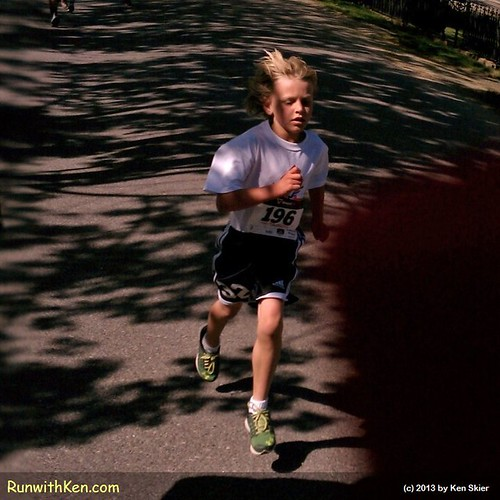 A young runners FLIES through the dappled sunlight.  At the Motif #1 5K in Rockport, MA.