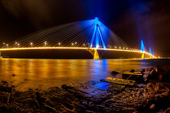 Rio bridge at night (dtsortanidis) Tags: street longexposure bridge blue light sea sky west reflection lamp rio yellow bulb architecture night port photoshop canon reflections dark bay interestingness interesting long exposure neon shadows purple nightshot harbour mark pylon full fisheye greece ii frame western 5d lamps hdr mk dimitris patras patra antirio peloponnese dimitrios charilaos photomatix peloponnisos trikoupis antirrio patraikos 815mm tsortanidis