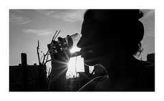 the woman with the two suns (dongga BS) Tags: street blackandwhite bw woman water girl wasser drinking streetphotography basel drinks sw frau schwarzweiss fluss trinken rhine rhein contrejour gegenlicht