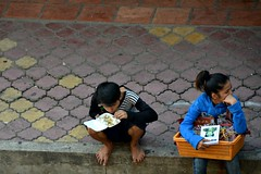 Sales Break (Pedestrian Photographer) Tags: life above street boy brick feet girl june kids children lunch fcc book dvd kid cambodia khmer basket rice box eating hawk bricks go spoon books container sidewalk pi bracelet noodles bracelets togo curb dvds selling phnom hawkers pp hawking penh 2013 dsc7701jpg dsc7701 lifepofpi