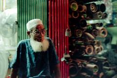 The Neverending Leisure... (Sheikh Shahriar Ahmed) Tags: street old light portrait film night analog 50mm store nikon candid muslim naturallight elderly elder fujifilm dhaka nikkor f18 bangladesh candidportrait nikonf6 busstand rampura tupi kupi af50mmf18d fujicolorc200 dhakadivision epsonv330 কুপি rampurabazar sheikhshahriarahmed