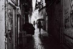 Alley Rain (OzGFK) Tags: light blackandwhite film night analog umbrella hongkong alley asia lane causewaybay pentaxmx