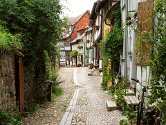 The Charm of the old Town and old Streets (Batikart) Tags: road street old city houses windows vacation urban orange plants green colors bicycle june yellow wall architecture stairs canon buildings germany bench outdoors deutschland town spring alley holidays europa europe day doors colours village citylife tranquility warped medieval romance historic journey stadt shutters blinds romantic historical recreation lantern relaxation cobbles ursula idyllic unescoworldheritage variation halftimbered frhling weltkulturerbe skew canonpowershot a610 sander fachwerkhaus quedlinburg frhjahr welterbe saxonyanhalt sachsenanhalt 100faves 2013 200faves 300faves cobbledstonestreet batikart outofsquare 201309
