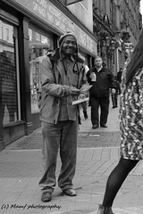 Leeds street man handing out flyers. ((c) MAMF photography..) Tags: man britain blackandwhite blackwhite bw biancoenero blancoynegro blanco blancoenero city candid dark england enblancoynegro flickrcom flickr google googleimages gb greatbritain greatphotographers greatphoto inbiancoenero image eastgateleeds leeds ls1 leedscitycentre