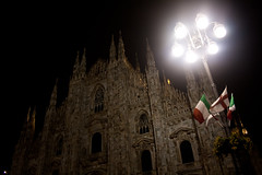 Duomo of Milan by Night (woofcode) Tags: flowers italy milan lamp night lights italian streetlight spires flags celebration duomo luminescence architectures twittering