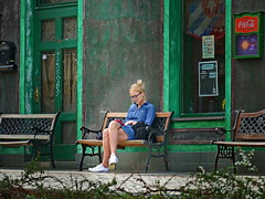 waiting (heinzkren) Tags: dame lady girl bank eingang lokal polen polska parkbank jeanskleid blondine fassade waiting reading woman frau window fenster türe door cocacola