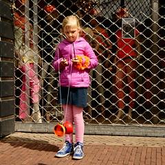 Concentration for the King (Hindrik S) Tags: street girls people orange playing color girl colorful child candid sony cpf meisje oranje queensday famke straat diabolo a300 nieuwestad sonyalpha nijstd dslra300 alpha300 boartsje sonyphotographing strjitte