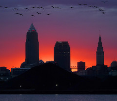 Cleveland skyline above the coal slag (joiseyshowaa) Tags: cleveland skyline sky scrapers morning dawn sun rise orange buildings coal port harbor lake erie water edgewater park fishing pier boat launch whiskey island thechallengefactory twilight