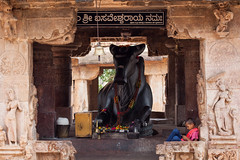 A modern Nandi and modern small kid in an heritage site (Scalino) Tags: india karnataka travel trip pattadakal heritage site chalukyas chalukya temple hindu kid playing mobile phone nandi cow statue black