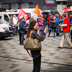 News-gathering girl (John Riper) Tags: johnriper street photography straatfotografie rotterdam netherlands candid john riper canon 6d 24105 l willemsplein people girl demonstration fnv news gathering vlog vlogging flags gucci alike bag filming video photo iphone smart phone